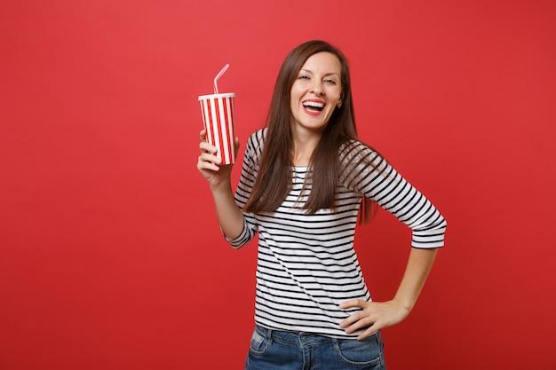 Ritratto di una giovane donna che ride in abiti casual a righe che tengono una tazza di plastica di cola o soda isolata su sfondo rosso brillante della parete. persone sincere emozioni, concetto di stile di vita. mock up copia spazio.