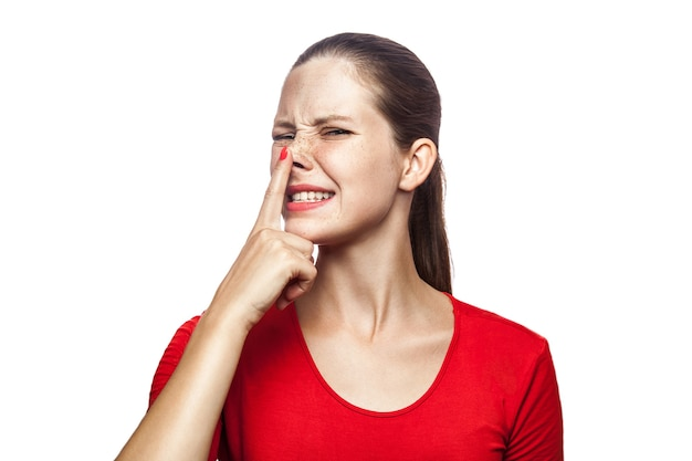 Ritratto di donna bugiarda in maglietta rossa con lentiggini che guarda in alto e si tocca il naso