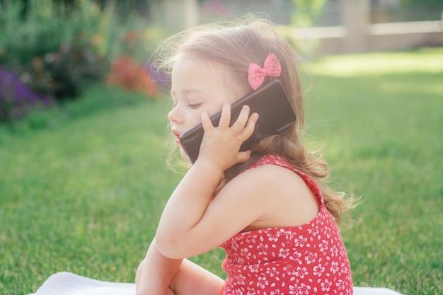 Ritratto di piccola ragazza 3-4 in vestiti rossi che si siede sulla coperta su erba verde e che parla sul telefono cellulare. bambini che usano i gadget