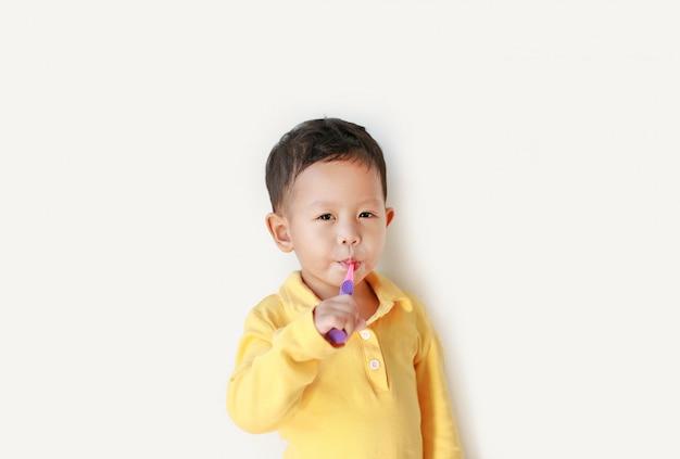 Ritratto dei denti di spazzolatura del piccolo ragazzo asiatico su fondo bianco