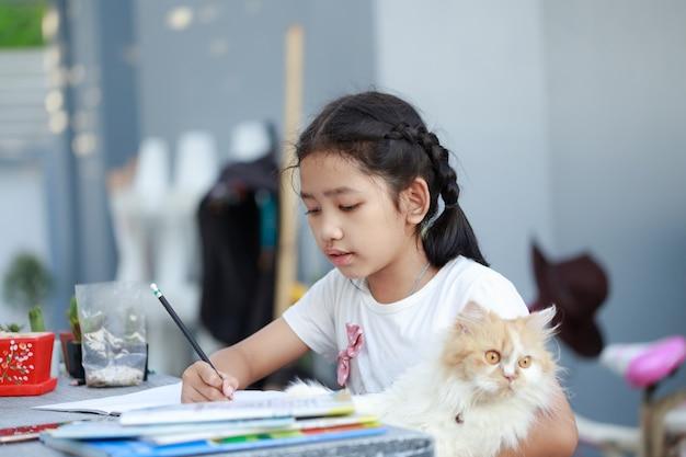 Ritratto di una piccola ragazza asiatica che fa i compiti mentre si tiene il suo gatto