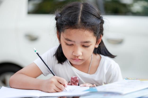 Ritratto di una piccola ragazza asiatica sta scrivendo, per imparare da casa, allontanamento sociale e concetto di quarantena, selezionare la profondità di campo della messa a fuoco