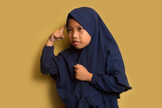 Il ritratto di una piccola ragazza musulmana asiatica di hijab pensa