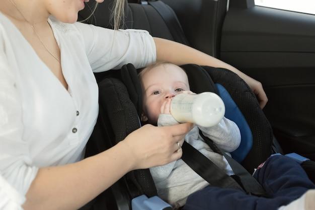 Ritratto di piccolo bambino che beve latte dalla bottiglia sul sedile posteriore dell'auto