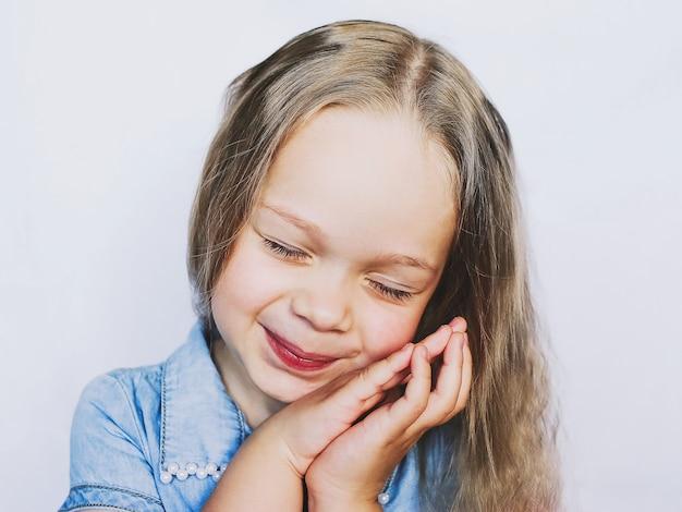 Ritratto di una piccola bellissima bambina, su sfondo bianco