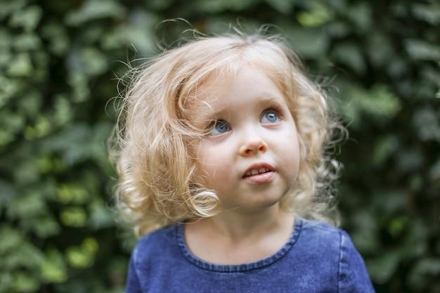 Ritratto di piccola bella ragazza caucasica sognante con capelli biondi ricci di 3 anni in abito di colore blu