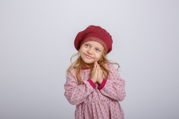 Ritratto di piccola ragazza bionda in berretto che chiede speranza isolata su fondo bianco