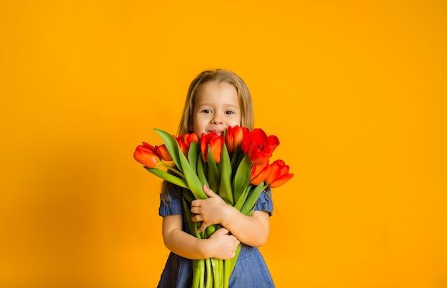 Ritratto di una bambina bionda in un vestito blu che tiene un mazzo di tulipani rossi su una parete gialla con una copia dello spazio