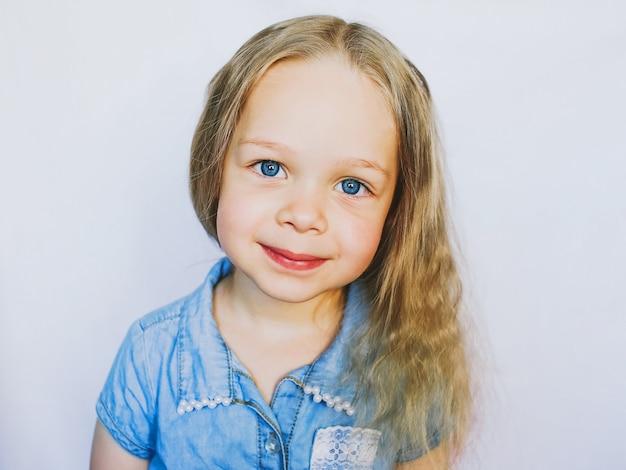 Ritratto di una piccola bambina bellissima dagli occhi azzurri, su sfondo bianco
