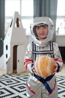 Ritratto di un ragazzino in costume da astronauta che tiene in mano la figura del pianeta e sorride alla telecamera in piedi nella stanza