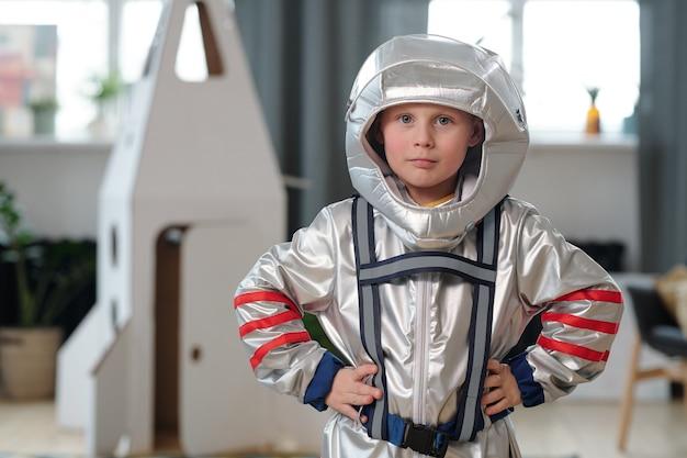 Ritratto di un ragazzino in costume da astronauta che guarda la telecamera mentre gioca a casa