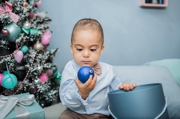 Ritratto di un ragazzino in una camicia blu con un palloncino giocattolo seduto su un letto contro un albero di natale