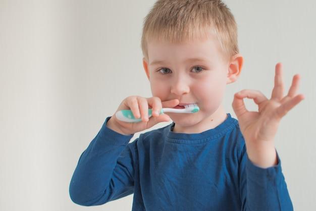 Ritratto del ragazzino che pulisce i denti sullo spazio luminoso e mostra il segno giusto. igiene dentale. copia spazio per il testo
