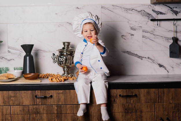 Ritratto di un ragazzino cucinare tenendo la padella in cucina. diverse occupazioni. isolato su sfondo bianco. fratelli gemelli
