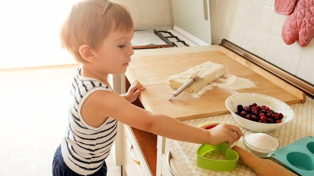 Ritratto del ragazzino che fa la pasta sul controsoffitto di legno della cucina. torte da forno per bambini o biscotti per la colazione