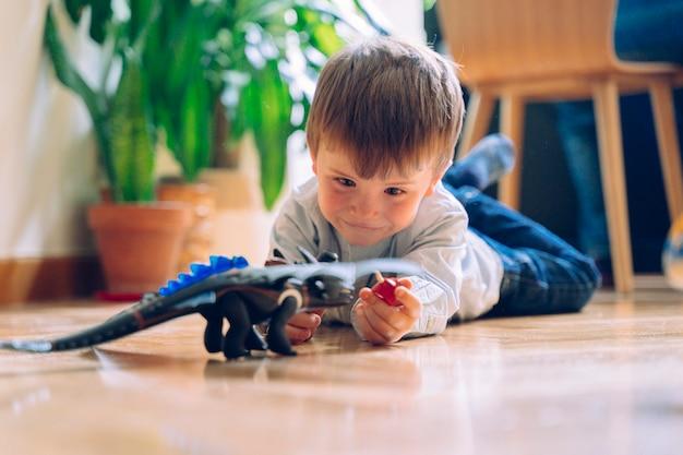Il ritratto di un ragazzino che gioca sul pavimento con la plastica gioca i dinosauri. giocattoli educativi per bambini.