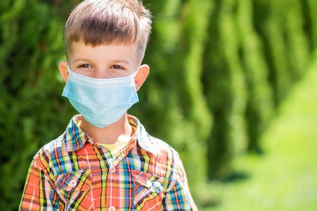 Ritratto di un ragazzino con maschera protettiva per strada durante la pandemia di coronavirus e covid - 19