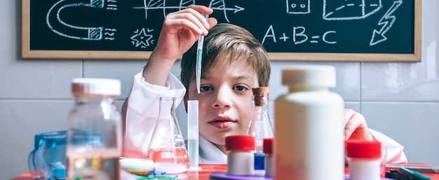 Ritratto di un ragazzino scienziato che estrae liquido dalla provetta dietro il tavolo con giocattoli chimici