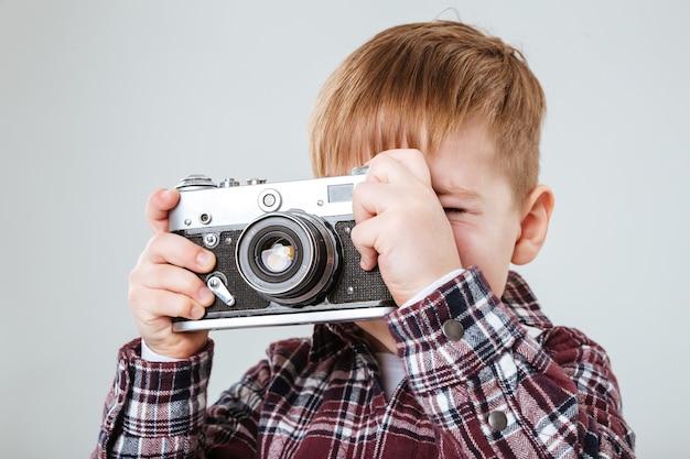 Ritratto di un ragazzino che scatta foto con una vecchia macchina fotografica vintage sul muro bianco