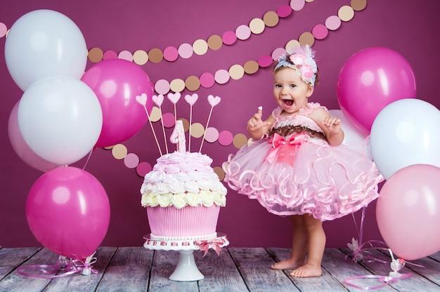 Ritratto di una piccola ragazza di compleanno allegro con la prima torta. mangiare la prima torta. torta smash.