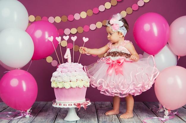 Ritratto di una piccola ragazza di compleanno allegro con la prima torta