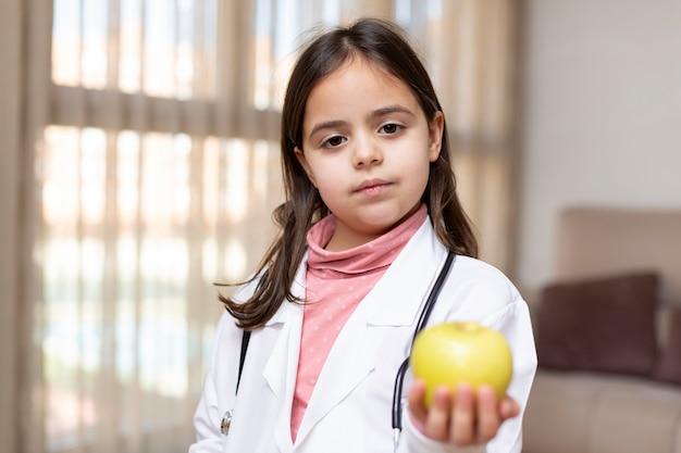 Ritratto di un bambino vestito da infermiera che mostra una mela in mano