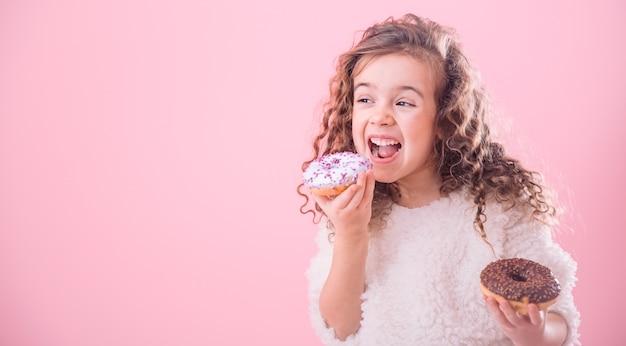 Ritratto di una bambina riccia che mangia le ciambelle