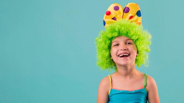 Ritratto di bambina carina in costume da clown con copia spazio