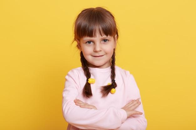Ritratto di piccola ragazza dai capelli scura con le mani giunte in posa sul giallo