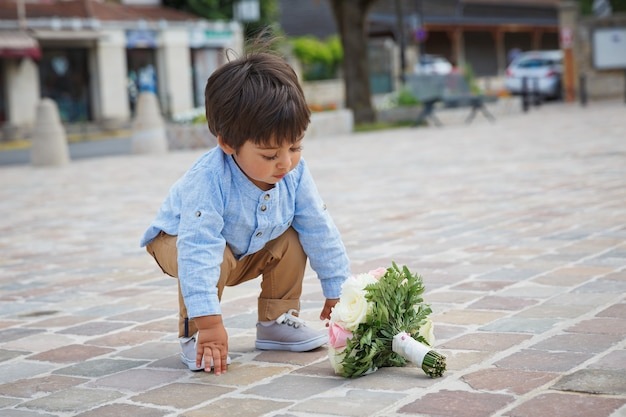 Ritratto di un bel neonato orientale che gioca all'aperto con un mazzo di fiori.