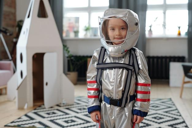 Ritratto di bambina in costume da astronauta che sorride alla telecamera mentre gioca nella stanza