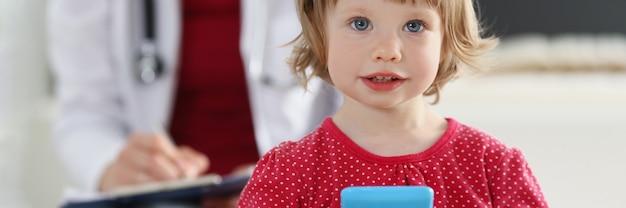 Ritratto di bambina su sfondo di medico in camice bianco. esame del bambino e concetto di assistenza medica