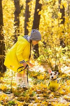 Ritratto di una bambina su uno sfondo di foglie arancioni e gialle in una giornata di sole autunnale