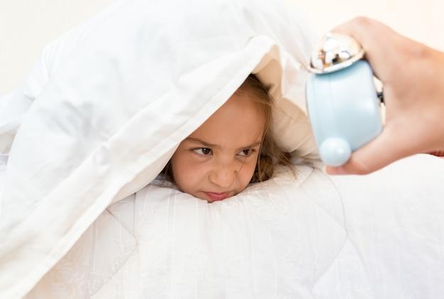 Ritratto di bambina che copre la testa con il cuscino e guarda la sveglia