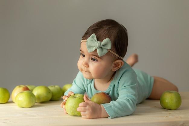 Ritratto di una bambina in un body verde su un tavolo di legno con mele verdi fresche. prodotti naturali per bambini. foto di alta qualità