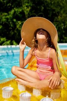 Ritratto di bambina in cappello che si rilassa in piscina, nuota sul materasso giallo gonfiabile e si diverte in acqua in vacanza con la famiglia, località di villeggiatura tropicale.