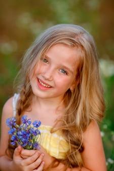 Ritratto di una bambina con in mano un mazzo di fiori blu in un campo in estate