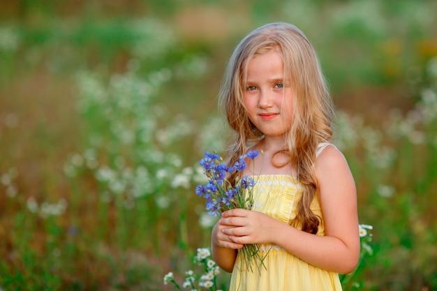 Ritratto bambina che tiene un mazzo di fiori in un campo in estate
