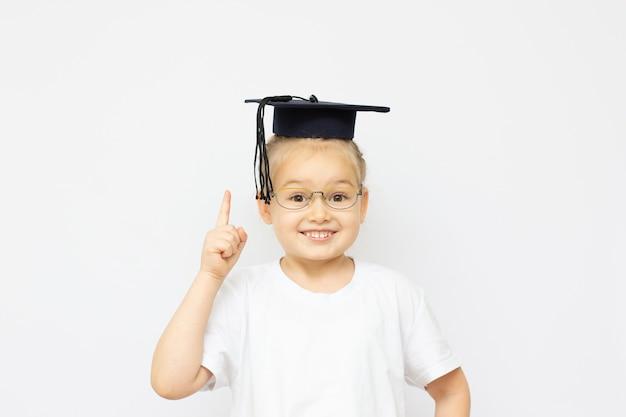 La bambina del ritratto sta portando il cappello e il sorriso laureati con la profondità di campo bassa del fuoco selezionata di felicità con lo spazio della copia per il concetto di istruzione