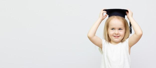 La bambina del ritratto sta portando il cappello e il sorriso laureati con felicità con lo spazio della copia per il concetto di istruzione