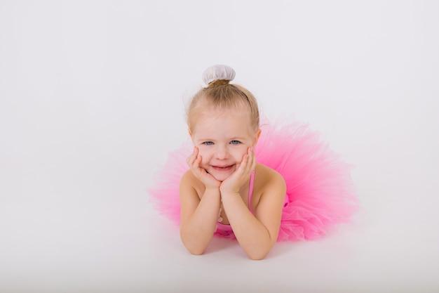 Ritratto di una bambina sdraiata in un abito rosa con una gonna tutu su un muro bianco