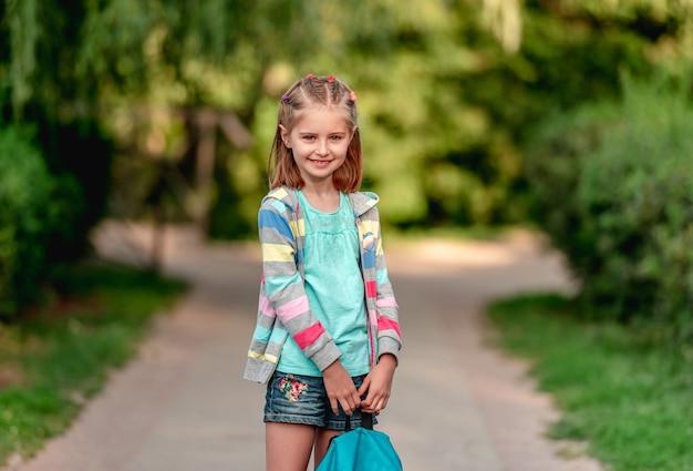 Ritratto di bambina in maschera che corre all'aperto dopo la scuola