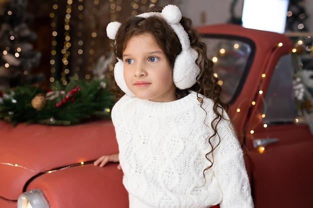 Ritratto della bambina vicino all'automobile rossa e alle luci di natale. buon natale e buone feste