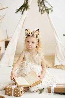 Un ritratto di una bambina vicino al wigwam e all'albero di natale che disimballa i regali di natale su una priorità bassa bianca