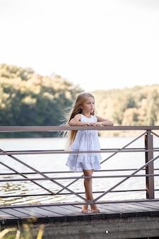 Ritratto di una bambina all'aperto in estate in riva al lago. bambina in abito estivo in riva al fiume.