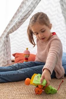 Bambina del ritratto che gioca con i giocattoli