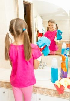 Ritratto di bambina che lucida lo specchio in bagno con detergente