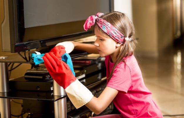 Ritratto di bambina in guanti di gomma che lucida il tavolo di vetro in soggiorno