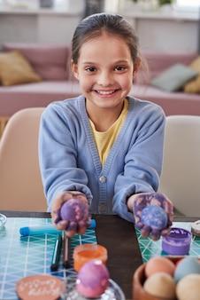 Ritratto di bambina che sorride alla macchina fotografica e mostra le uova dipinte nelle sue mani per le vacanze di pasqua