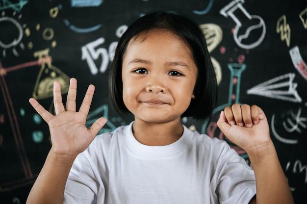 Ritratto bambina in piedi e mostra il dito con il numero cinque e il gesto zero
